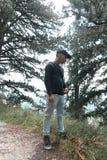 Caminhante novo que olha lateralmente na frente dos pinheiros imagens de stock