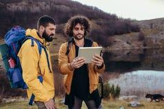 Caminhante perdido que olha a maneira através do mapa na tabuleta digital durante a caminhada imagens de stock