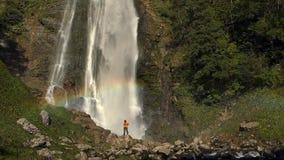 Caminhante perto da cachoeira com arco-íris Metragem do movimento lento filme