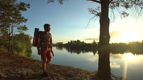 Caminhante que anda ao longo do banco de rio no lugar magnífico, apreciando a vista bonita vídeos de arquivo