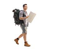 Caminhante que anda e que guarda um mapa genérico fotos de stock