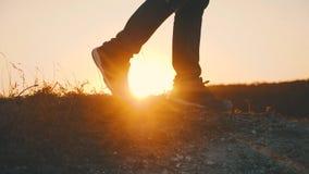 Caminhante que anda fora no por do sol na rocha Os pés em botas trekking vão ao longo do cume da montanha contra o contexto de filme