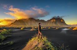 Caminhante que aprecia o por do sol em Vestrahorn e em sua praia preta da areia em Islândia fotos de stock royalty free