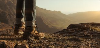 Caminhante que aprecia o por do sol nas montanhas Fotos de Stock Royalty Free