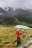 Caminhante que caminha no passeio na montanha com a trouxa na chuva Imagens de Stock Royalty Free