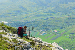 Caminhante que descansa em rochas nas montanhas Imagem de Stock