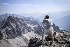Caminhante que fotografa na cimeira dos cumes de Allgau Foto de Stock