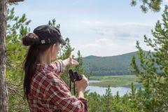 Caminhante que guarda binóculos e que aponta os dedos na natureza, no lago, na montanha e nas árvores, fim acima imagens de stock royalty free