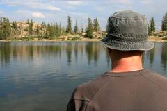 Caminhante que olha para fora sobre o lago fotografia de stock
