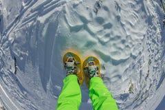 Caminhante que olha sobre seus sapatos de neve na paisagem bonita nas montanhas francesas durante o por do sol Imagens de Stock Royalty Free