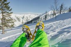 Caminhante que olha sobre seus sapatos de neve na paisagem bonita nas montanhas francesas durante o por do sol Fotografia de Stock
