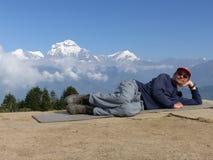 Caminhante que relaxa em Poon Hill, escala de Dhaulagiri, Nepal imagens de stock royalty free