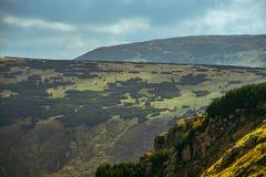 Caminhante que senta-se ao lado de um penhasco em uma montanha gigante Fotografia de Stock