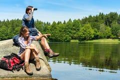 Caminhantes adolescentes que birdwatching no lago imagens de stock royalty free