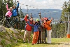 Caminhantes felizes que alcançam sua parte superior da montanha do objetivo Fotografia de Stock Royalty Free