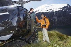 Caminhantes com o helicóptero na parte superior da montanha fotografia de stock