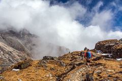 Caminhantes da montanha que andam em nuvens bonitas do terreno gramíneo Imagens de Stock Royalty Free