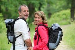 Caminhantes de sorriso na floresta que apreciam a viagem fotografia de stock