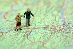 Caminhantes diminutos que estão em um mapa. Fotos de Stock Royalty Free