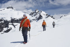 Caminhantes juntados pela linha da segurança em montanhas nevado Imagem de Stock Royalty Free
