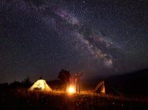 Caminhantes novos dos pares que descansam perto da barraca iluminada, acampando nas montanhas na noite sob o céu estrelado Imagem de Stock Royalty Free