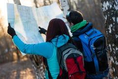 Caminhantes novos dos pares que olham o mapa Fotografia de Stock Royalty Free