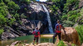 Caminhantes pela cachoeira do campo Fotos de Stock Royalty Free