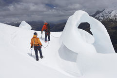 Caminhantes pela formação de gelo nas montanhas Imagens de Stock Royalty Free