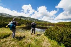 Caminhantes próximo um lago nas montanhas Fotografia de Stock