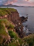 Caminhantes que admiram o por do sol dos penhascos íngremes na Irlanda ocidental Imagens de Stock