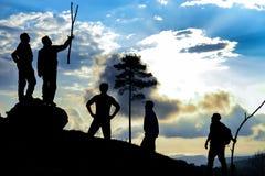Caminhantes que alcançam a cimeira no por do sol Fotografia de Stock Royalty Free