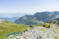 Caminhantes que descansam na cimeira da montanha, caro panorama Fotos de Stock Royalty Free