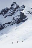 Caminhantes que dirigem para o pico distante na neve Fotografia de Stock Royalty Free