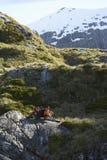 Caminhantes que sentam-se em pedregulhos no vale da montanha imagens de stock