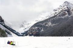 Caminhantes que sentam-se no lago alpino congelado fotografia de stock royalty free