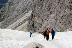 Caminhantes que trekking na neve Sassolungo, Itália Fotografia de Stock Royalty Free