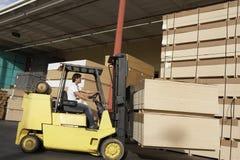 Caminhão de empilhadeira de funcionamento do trabalhador manual na indústria da madeira serrada Foto de Stock