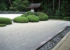 Caminho exterior japonês do jardim com arbustos verdes e fundo de pavimentação de pedra fotografia de stock