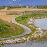 Caminho pavimentado quadrado do quadro que curva-se ao longo da costa rochosa e gramínea do lago sob o céu nebuloso imagens de stock