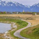Caminho pavimentado quadrado que curva-se ao longo da costa rochosa e gramínea do lago sob o céu nebuloso fotografia de stock