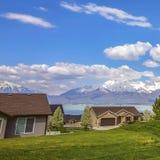 Caminho quadrado do quadro em um terreno gramíneo vasto que conduz às casas na frente de um lago fotos de stock royalty free