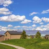 Caminho quadrado em um terreno gramíneo vasto que conduz às casas na frente de um lago foto de stock royalty free