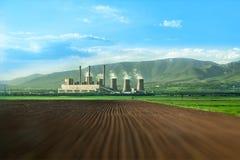 Camini enormi della centrale elettrica termica su un campo Fotografie Stock Libere da Diritti