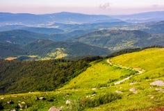 Camino abajo de la colina adentro al valle de montañas azules Foto de archivo
