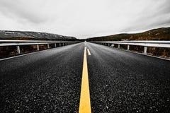 Camino abandonado a través del desierto de Noruega con asfalto, el bosque y las montañas Fotografía de archivo