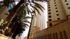 Camino ancho con las palmas altas y los edificios modernos existencias Palmeras y edificios retros típicos del estilo del art déc almacen de video