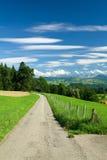 Camino, cerca vieja a lo largo de ella, campos verdes y mountai Foto de archivo
