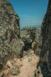 Camino cercado por las rocas grandes y los arbustos secos en cumbre imagen de archivo libre de regalías