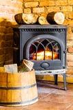 Camino con la fiamma e la legna da ardere del fuoco nell'interno del barilotto heating immagini stock libere da diritti