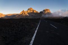 Camino con la montaña en puesta del sol Fotografía de archivo